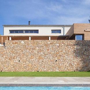 Idée de décoration pour une grande façade en bois blanche design à un étage avec un toit plat.