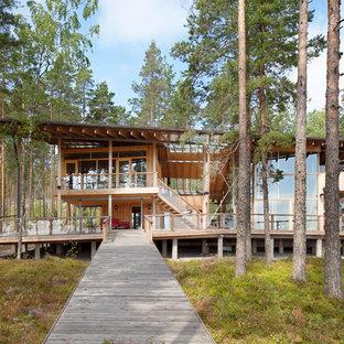 Idées déco pour une grande façade de maison marron scandinave à un étage avec un toit plat et un toit végétal.