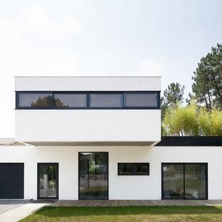 Idées déco pour une façade de maison blanche contemporaine de taille moyenne et à un étage avec un toit plat.