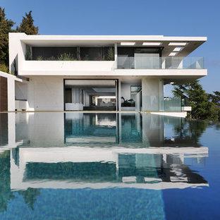Idées déco pour une façade de maison blanche moderne à un étage et de taille moyenne avec un toit plat.