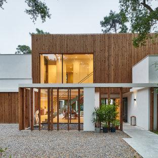 Inspiration pour une grand façade de maison multicolore design à un étage avec un revêtement mixte et un toit plat.