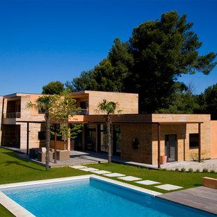 Modelo de fachada de casa naranja, actual, grande, de dos plantas, con revestimiento de madera, tejado plano y techo verde
