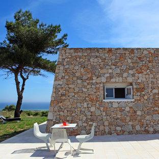 Diseño de fachada roja, marinera, pequeña, de una planta, con revestimiento de piedra y tejado plano