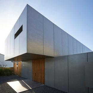 Réalisation d'une grand façade de maison grise design à un étage avec un toit plat.