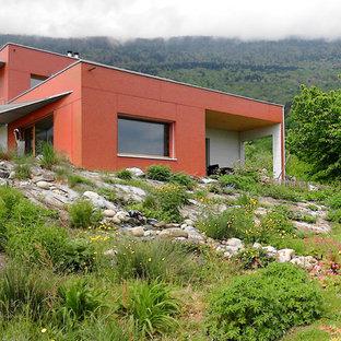 Réalisation d'une façade de maison rouge design de taille moyenne et à un étage avec un toit plat.