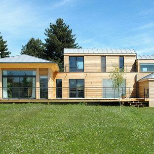 Idée de décoration pour une grande façade de maison beige design à niveaux décalés avec un toit à quatre pans.