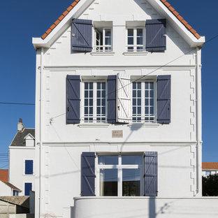 Ejemplo de fachada de casa pareada blanca, costera, grande, de tres plantas, con revestimiento de piedra, tejado a dos aguas y tejado de teja de barro
