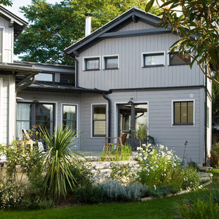 Cette image montre une façade de maison grise nordique à un étage et de taille moyenne avec un toit à deux pans.