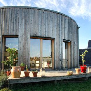 Exemple d'une façade en bois marron tendance de taille moyenne et de plain-pied avec un toit plat.