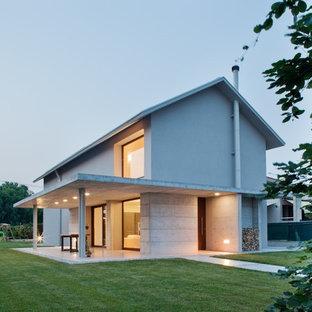 Esempio della facciata di una casa grande grigia contemporanea a due piani con rivestimenti misti e tetto a capanna