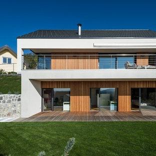Esempio della facciata di una casa unifamiliare grande bianca contemporanea a due piani con rivestimento in legno e tetto a capanna