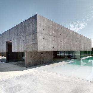 Esempio della facciata di una casa ampia grigia moderna a due piani con rivestimento con lastre in cemento e tetto piano