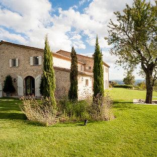 Esempio della facciata di una casa country a due piani con rivestimento in pietra e tetto a capanna