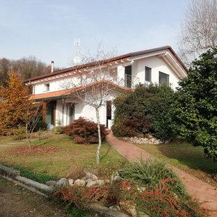Foto de fachada de casa blanca, clásica, de tamaño medio, de dos plantas, con revestimiento de estuco, tejado a doble faldón y tejado de teja de barro