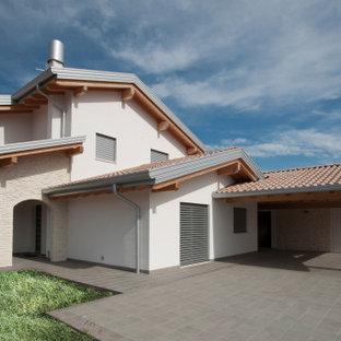 Idéer för stora funkis beige hus, med två våningar, sadeltak och tak med takplattor