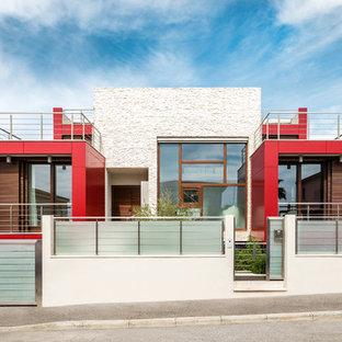 Esempio della facciata di una casa unifamiliare rossa contemporanea con rivestimenti misti e tetto piano