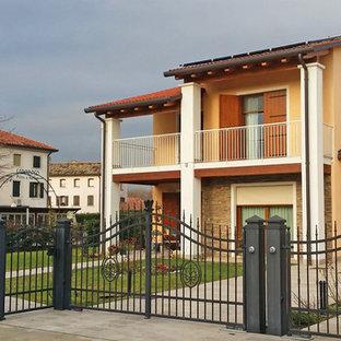 Imagen de fachada de casa bifamiliar amarilla, romántica, extra grande, de dos plantas, con revestimiento de madera