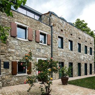 Foto della facciata di una casa unifamiliare beige country a tre o più piani con rivestimento in pietra e tetto piano