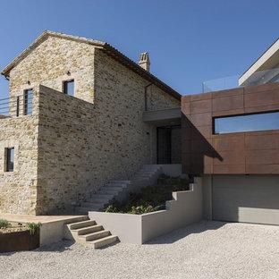 Esempio della facciata di una casa contemporanea a due piani con rivestimento in pietra, tetto a capanna e copertura in tegole
