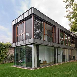 Foto della facciata di una casa unifamiliare grigia contemporanea a due piani con rivestimento in vetro e tetto piano