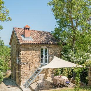 Ejemplo de fachada de casa marrón, de estilo de casa de campo, pequeña, de dos plantas, con revestimiento de piedra, tejado a dos aguas y tejado de teja de barro