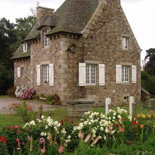 Cette image montre une façade en pierre traditionnelle à un étage et de taille moyenne avec un toit à quatre pans.