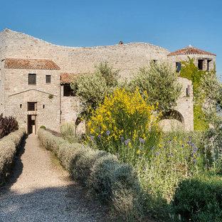 Ispirazione per la facciata di una casa grande beige mediterranea a tre o più piani con rivestimento in pietra