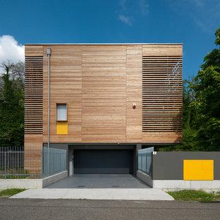 Esempio della facciata di una casa contemporanea a tre o più piani di medie dimensioni con rivestimento in legno e tetto piano