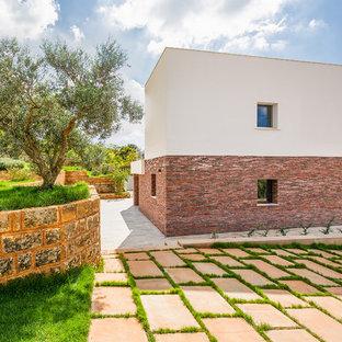 Diseño de fachada blanca, mediterránea, de dos plantas, con revestimientos combinados y tejado plano