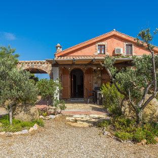 Esempio della facciata di una casa rossa mediterranea a due piani di medie dimensioni con rivestimenti misti e tetto a capanna
