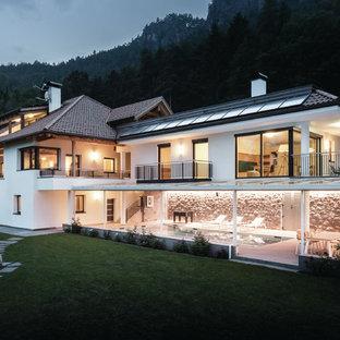 Immagine della facciata di una casa unifamiliare bianca contemporanea a due piani con rivestimenti misti, tetto a padiglione e copertura in tegole