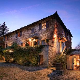 Foto della facciata di una casa unifamiliare beige mediterranea a tre piani con rivestimento in pietra