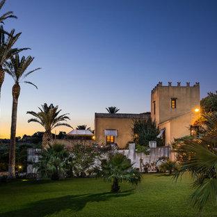 Idee per la villa gialla mediterranea a due piani con tetto a capanna e copertura in tegole