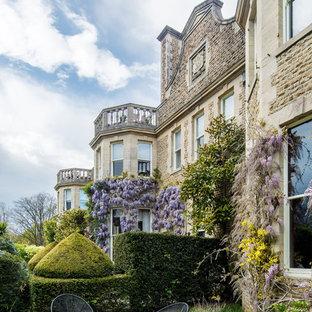 Пример оригинального дизайна: огромный, трехэтажный, кирпичный, бежевый частный загородный дом в викторианском стиле