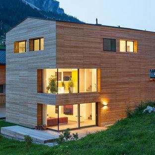 Immagine della facciata di una casa contemporanea a tre o più piani con rivestimento in legno e tetto a capanna