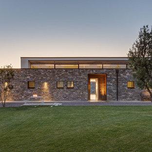Foto della facciata di una casa moderna a un piano di medie dimensioni in pietra e intonaco con tetto piano