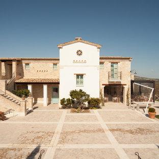 Idee per la villa arancione mediterranea a due piani con rivestimento in mattoni, tetto a capanna, copertura in tegole e scale