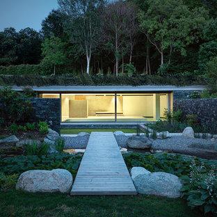 Idee per la facciata di una casa contemporanea a un piano con tetto piano e rivestimento in vetro