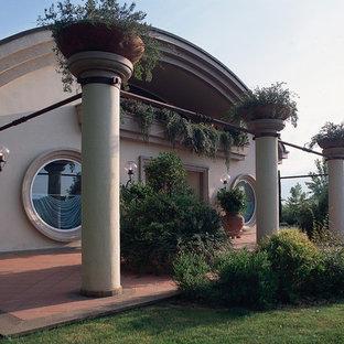 Foto de fachada gris, bohemia, extra grande, de dos plantas, con revestimiento de hormigón y tejado a cuatro aguas