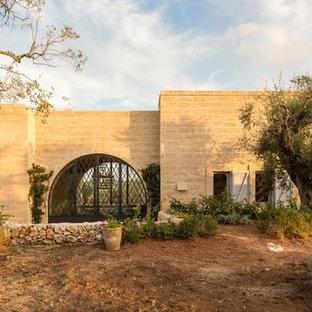 Ispirazione per la facciata di una casa beige mediterranea con rivestimento in pietra