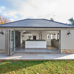 Esempio della facciata di una casa unifamiliare piccola grigia contemporanea a un piano con rivestimenti misti e tetto a padiglione