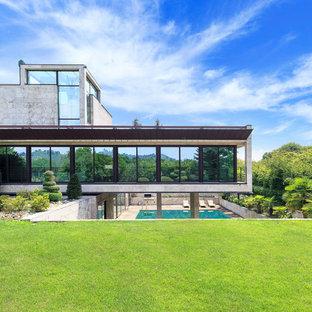 Idee per la villa grigia moderna a tre piani con rivestimento in pietra e tetto piano