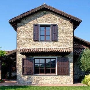 Immagine della facciata di una casa country a due piani di medie dimensioni con rivestimento in mattoni e tetto a capanna