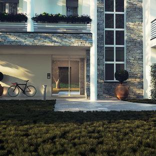 На фото: трехэтажный, белый многоквартирный дом в современном стиле с облицовкой из камня, плоской крышей и крышей из смешанных материалов