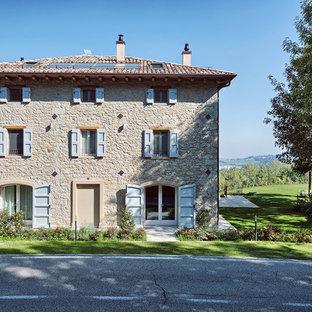 Ispirazione per la facciata di una casa bifamiliare grande beige in campagna a tre o più piani con rivestimento in pietra e copertura in tegole