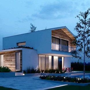 Foto della facciata di una casa bianca contemporanea a due piani di medie dimensioni con rivestimenti misti e tetto a capanna
