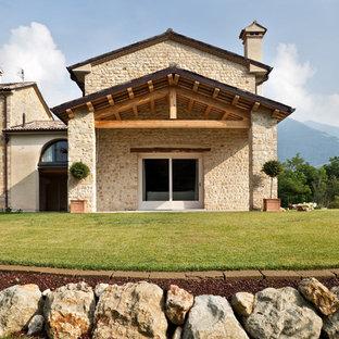 Esempio della facciata di una casa grande beige country a tre o più piani con rivestimento in pietra e tetto a capanna
