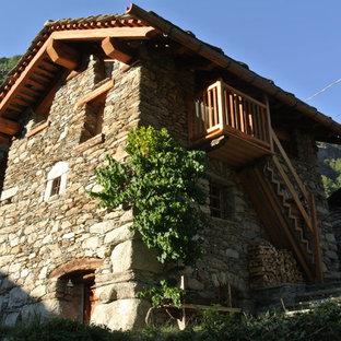 Foto della facciata di una casa unifamiliare piccola multicolore rustica a tre o più piani con rivestimento in pietra, tetto a capanna e copertura mista
