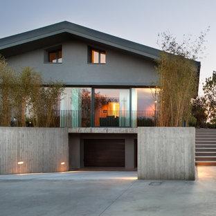 Idee per la facciata di una casa grande grigia contemporanea a due piani con rivestimento in cemento e tetto a capanna