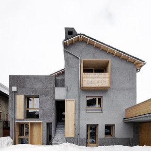 Foto della facciata di una casa unifamiliare grigia contemporanea a tre o più piani con tetto a capanna